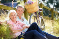 Middle Aged Couple Relaxing On Country Cycle Ride Royalty Free Stock Photos - 35778788