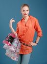 Girl In An Orange Shirt And Jeans With Shopping Bags On A Blue B Royalty Free Stock Photography - 35839297