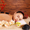 Adult Woman Relaxing In Spa Salon With Hot Stones On Back Stock Image - 35879371