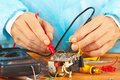 Master Checks The Electronic Components Of Device With Multimeter Stock Photos - 36000923