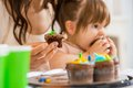 Mother Holding Cupcake With Girl Eating Cake Stock Photo - 36084220