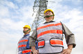 Two Workers Standing Before Electrical Power Tower Royalty Free Stock Photos - 36173878