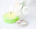 Pair Of Wedding Rings With Lit Green Candle Royalty Free Stock Photography - 36243357