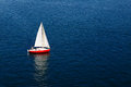 A Lone White Sail On A Calm Blue Sea Stock Image - 36552291