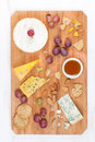 Assorted Soft Cheeses, Grapes, Nuts And Honey On Wooden Board Stock Photo - 36603030