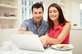 Couple Looking At Laptop Over Breakfast Stock Photography - 36615322