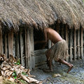 The Woman In A Traditional Skirt Hides In A Hut. Royalty Free Stock Photography - 36945207