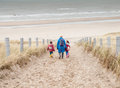 Woman And Two Small Children Walking Down To The Beach Stock Photos - 36976943