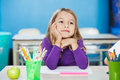 Thoughtful Girl With Hand On Chin Sitting At Desk Stock Photos - 36993773