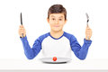 Young Boy Holding Fork And Knife With Cherry Tomato In Front Of Stock Images - 36998984