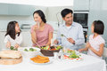 Young Family Of Four Enjoying Healthy Meal In Kitchen Royalty Free Stock Image - 37197506