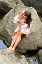 Young Mother And Her Son Sitting On A Rock Royalty Free Stock Photos - 37283568