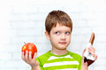 Small Child Chooses Chocolate Or Apple Stock Photos - 37513563