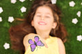 Little Girl Laying In Meadow And Reaching To Touch Butterfly Royalty Free Stock Photography - 37578547
