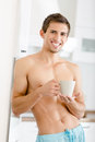 Half-naked Young Man With Cup Of Tea At Kitchen Royalty Free Stock Image - 37636406