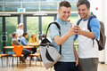 Two Male Students In Classroom Reading Message On Phone Stock Photography - 37720342
