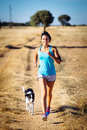 Woman And Dog Running In Rural Countryside Path Royalty Free Stock Photography - 37785557