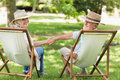 Relaxed Mature Couple Sitting In Deck Chairs At Park Stock Photo - 37826180