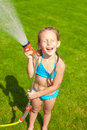 Happy Cute Little Girl Pouring Water From A Hose Royalty Free Stock Photo - 38018455