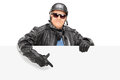 Mature Biker Pointing On A Blank Panel Stock Image - 38331701