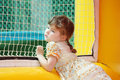Little Girl Stands In Yellow Bouncy Castle Stock Photos - 38502573