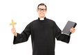 Catholic Priest Holding Holy Bible And A Golden Cross Stock Photos - 38542273