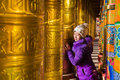 Young Women And Buddhist Prayer Wheels Royalty Free Stock Image - 38567656