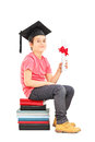 Boy Sitting On Stack Of Books And Holding Diploma Royalty Free Stock Image - 38657796