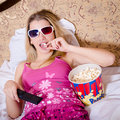 Blond Young Woman In Color Pajamas Lying In Bed With TV Remote Control In Hand Watching Movie In 3D Glasses And Eating Popcorn Royalty Free Stock Photo - 38971705