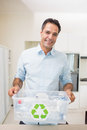 Smiling Man Carrying Recycling Container In Kitchen Stock Images - 39215434