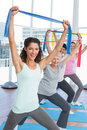 Class Holding Up Exercise Belts At Yoga Class Royalty Free Stock Photography - 39231097