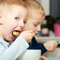 Boys Kids Children Eating Corn Flakes Breakfast Meal At The Table Stock Images - 39379744