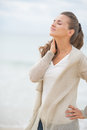 Portrait Of Relaxed Young Woman On Cold Beach Royalty Free Stock Photography - 39498667