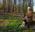 Old Woman Sitting On A Stump Royalty Free Stock Photos - 39532638