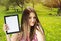 Beautiful Young Woman In Park Showing Tablet Computer Royalty Free Stock Photos - 39599588