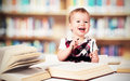 Funny Baby Girl In Glasses Reading A Book In A Library Stock Photo - 39611320