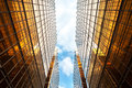 Upwards Perspective Of Symmetrical Contemporary Skyscrapers, With Blue Sky And White Clouds Stock Image - 39858851