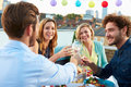 Group Of Friends Eating Meal On Rooftop Terrace Stock Images - 40097194