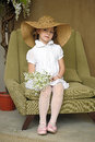 Little Girl With A Smile In A Wide-brimmed Straw Hat In A Bouquet Of White Lilies Of The Valley In The Hands Royalty Free Stock Photo - 40144495