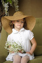 Little Girl With A Smile In A Wide-brimmed Straw Hat In A Bouquet Of White Lilies Of The Valley In The Hands Royalty Free Stock Image - 40144726