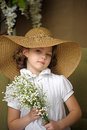 Little Girl With A Smile In A Wide-brimmed Straw Hat In A Bouquet Of White Lilies Of The Valley In The Hands Royalty Free Stock Image - 40144826