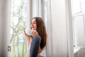 Young And Cute Lady Dreaming On The Windowsill With Cup Of Coffe Royalty Free Stock Photography - 40146817