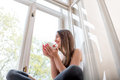 Young And Cute Lady Sitting On The Windowsill And Looking Out Th Royalty Free Stock Images - 40146989