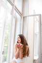 Young And Cute Lady Sitting On The Windowsill And Looking Out Th Royalty Free Stock Image - 40147366