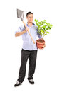 Man Holding A Shovel And A Plant Stock Photo - 40257640