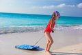 Little Adorable Girl Pulls A Surfboard On White Shore Stock Photo - 40447890