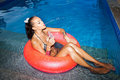 Woman Floating In Inner Tube In Pool And Drinking Water Stock Photo - 40537580