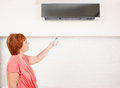 Woman Holding A Remote Control Air Conditioner Stock Photography - 40656862