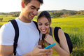 Young Couple Outdoors Looking At The Mobile Phone Royalty Free Stock Image - 40663116