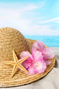 Sun Hat And Flowers On The Beach Stock Photography - 40722542